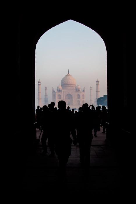 Uma multidão caminhando em direção ao Taj Mahal emoldurada por um arco