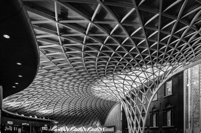 Fotografia em preto e branco do telhado da estação ferroviária King's Cross de Londres
