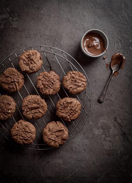 Camada plana de cookies resfriando em um fio próximo a uma tigela de chocolate
