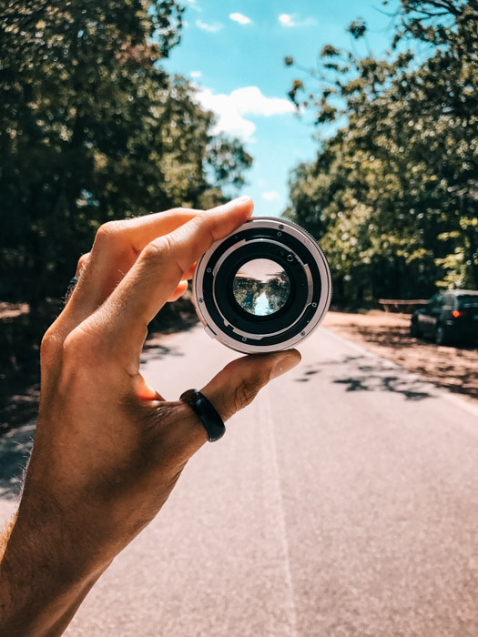 A hand holding up camera lens showing a city road with trees on the side