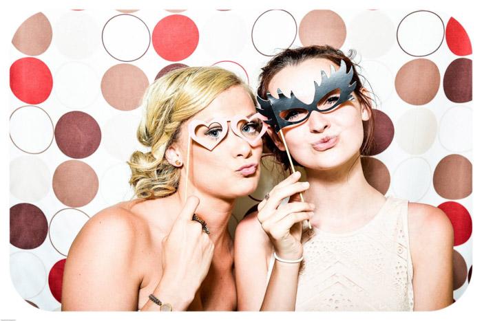Duas garotas posando com máscaras em frente a um fundo fotográfico colorido