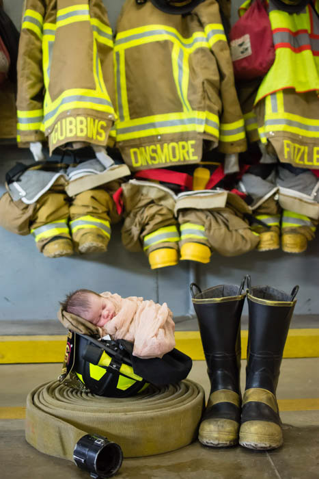 a newborn baby posed with fireman paraphernalia