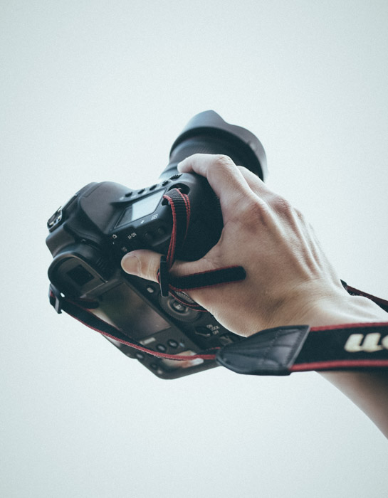 A person holding a Canon DSLR