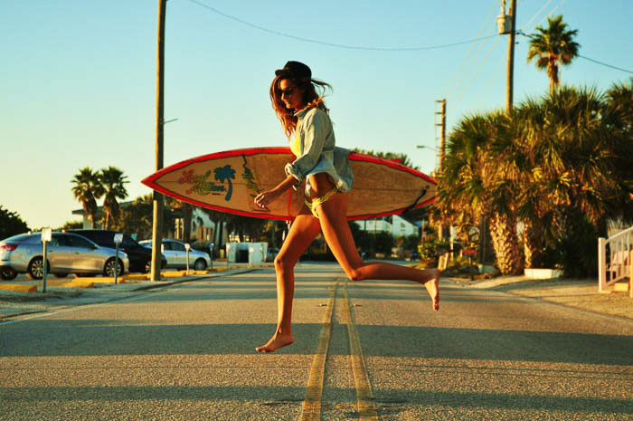 A fashion photography shot of a female model walking with a surfboard
