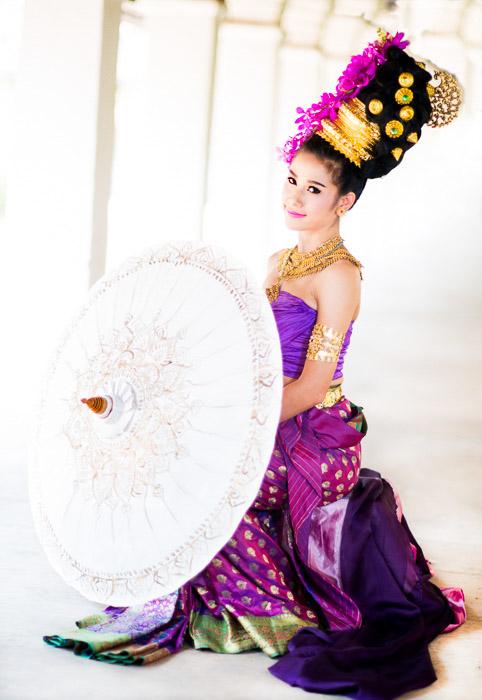 A dancer in costumer holding an umbrella