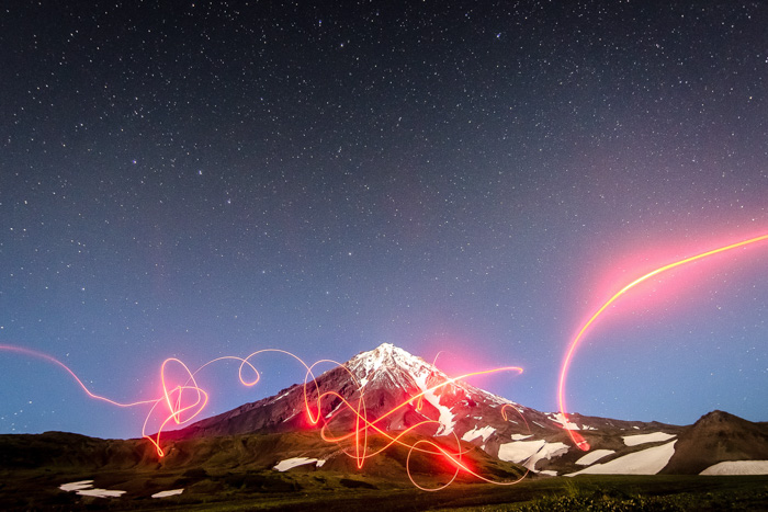 Light graffiti in front of a snowy mountainous landscape