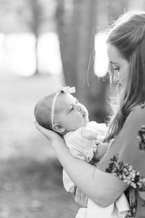 Black and white newborn photography of a woman holding a baby