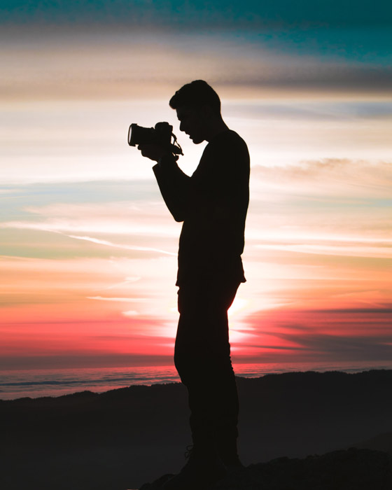 A silhouette of a photographer holding a DSLR