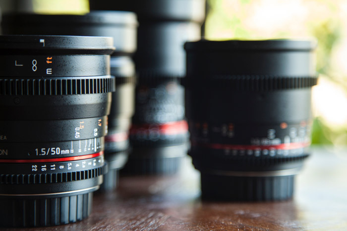 Various lenses resting on a wooden table