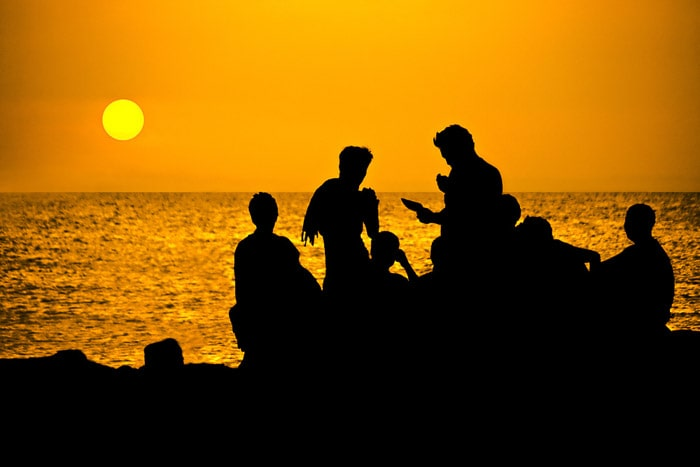 Silhouette of a group of people by the sea