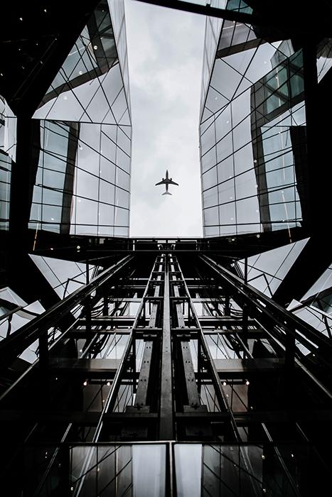 Vista aérea de um avião voando sobre um edifício com telhado de vidro