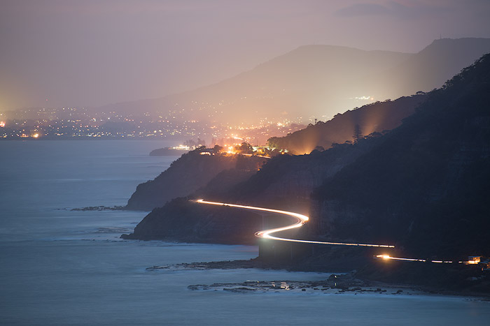telephoto shot of an ethereal coastal road with mountains and city lights in the background, shot with a Nikon 70-300/4.5 - 5.6 at 260 mm