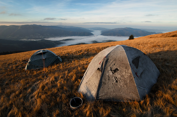 ultra wide crop photo of two tents pitched on grass with a stunning landscape scene in the background, shot with a Nikon 10-24 lens