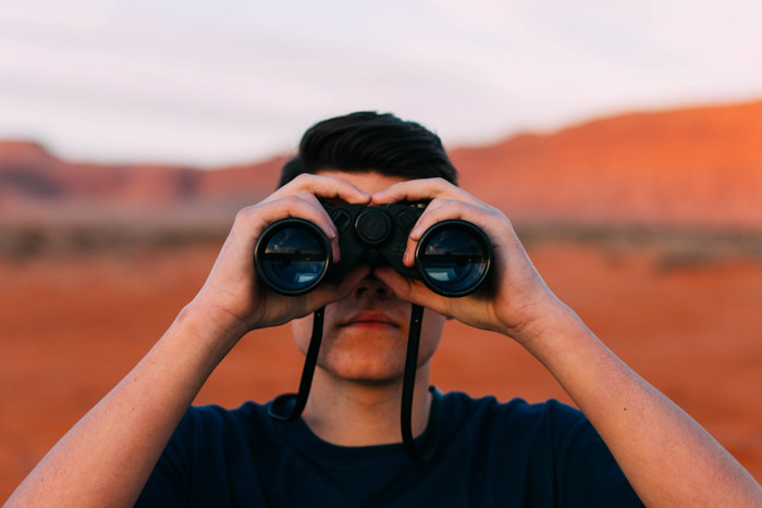 A photographer with binoculars