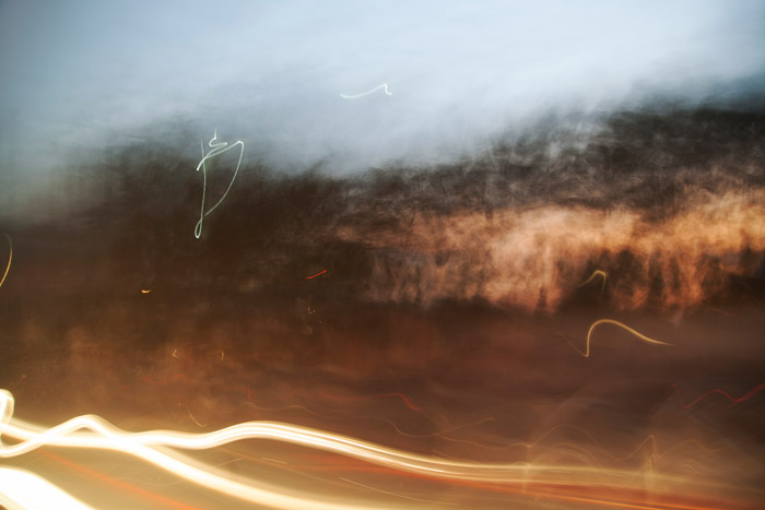 Slow-shutter photograph of blurry light trails and bushes. taken while travelling a highway at dusk. Abstract photography ideas.