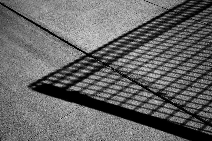 Black and white photography of the shadow of a wire mesh fence on concrete. Abstract photography ideas.
