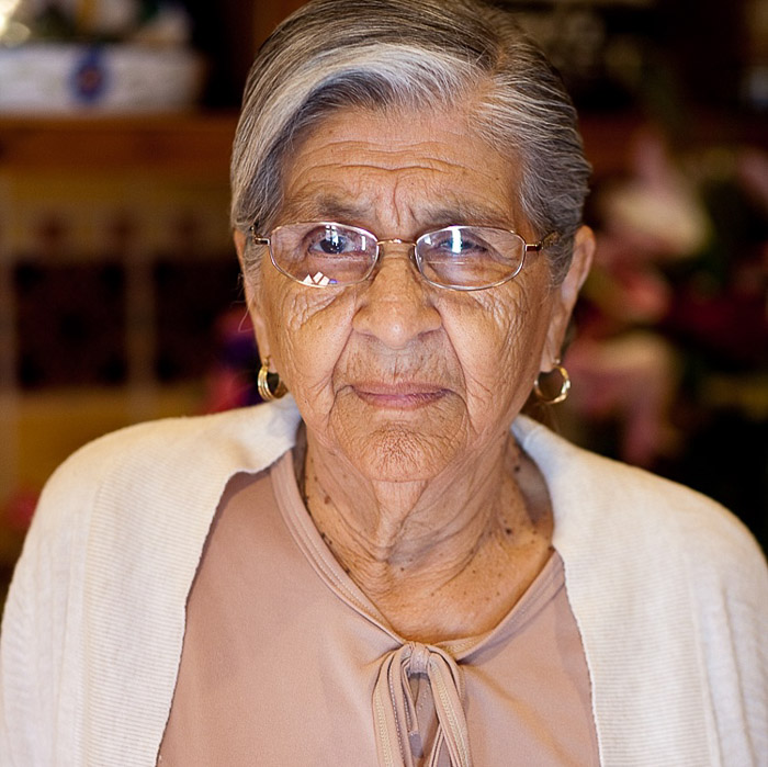An elderly wedding guest with glasses looks at the camera. Amateur wedding photographer