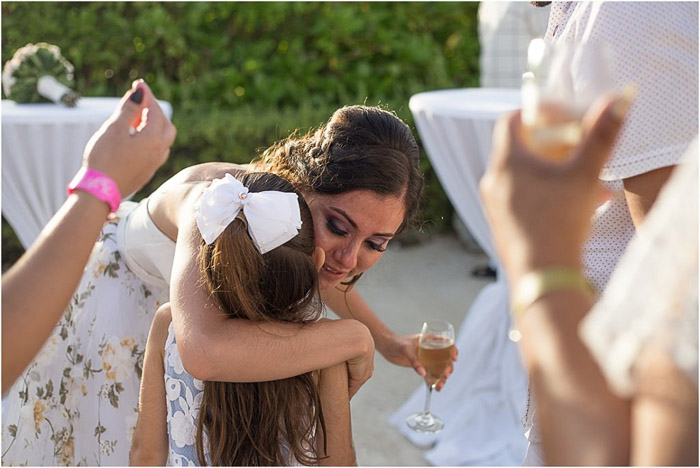 Bride hugging young flowergirl amidst guests clapping. Amateur wedding photography.