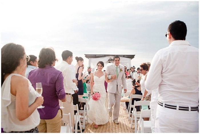a newlywed couple walking down the aisle of an outdoor beach wedding. Amateur wedding photography.