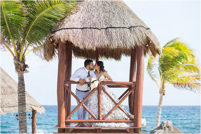 a newlywed couple kissing in a hut on the beach on a clear day. Amateur wedding photography.