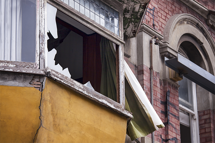 Close up of the facade of a building showing 2 windowsills, one with the glass broken. Architecture photo after the earthquakes in Christchurch, New Zealand.
