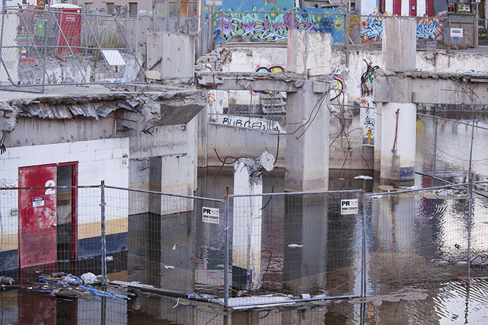 Busy scene of broken buildings, fences and water - architectural photography after the earthquakes in Christchurch, New Zealand.