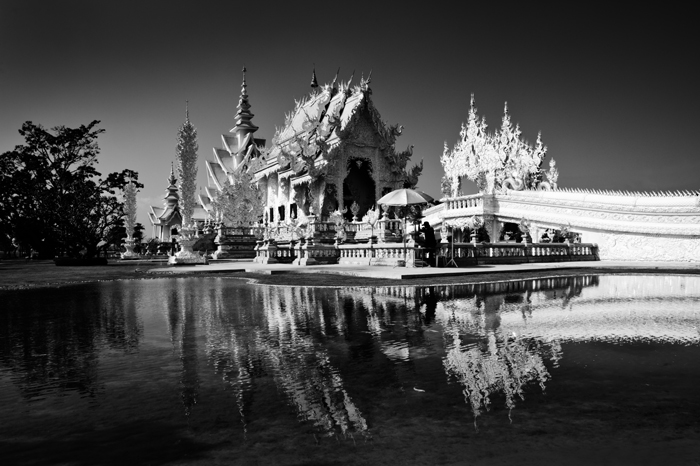 Black and white travel photograph of the White Temple in Chiang Rai, Thailand, the building reflected in the water below