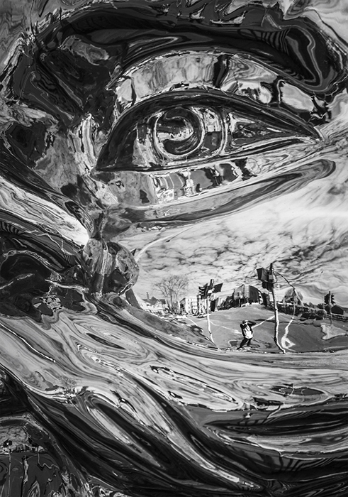 Black and white photo with photographer's reflection in 'Reflective Lullaby (John)' sculpture by Gregor Kregar. Creative street photography