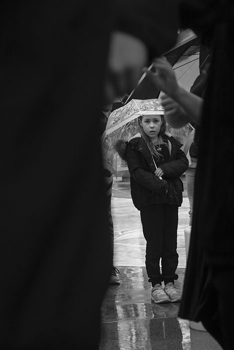 Black and street photo of a little girl with umbrella framed by the silhouette of people in the foreground. Creative street photography