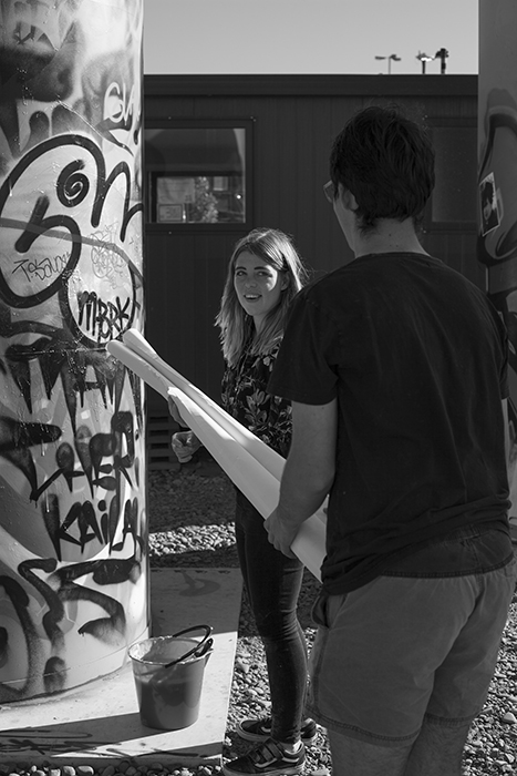 Black and white photo of CHUZKOS artists installing a photographic street art exhibition. Creative street photography