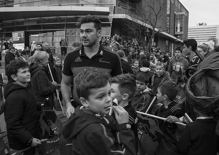 Blavk and white street photography of a crowd surrounding their winning rugby team.