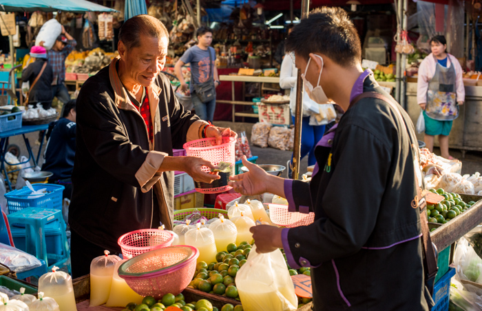Two Asian men in a market trading