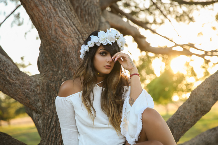 Bright and airy portrait of a girl in white dress with white flowers in her hair, sitting in front of a tree. Improve your photography skills today