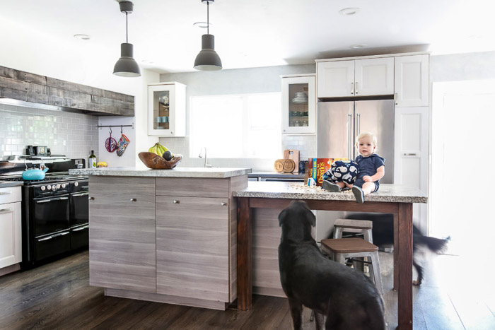 Interior photography of a bright and airy kitchen interior, with wooden furniture, a baby and a black dog.