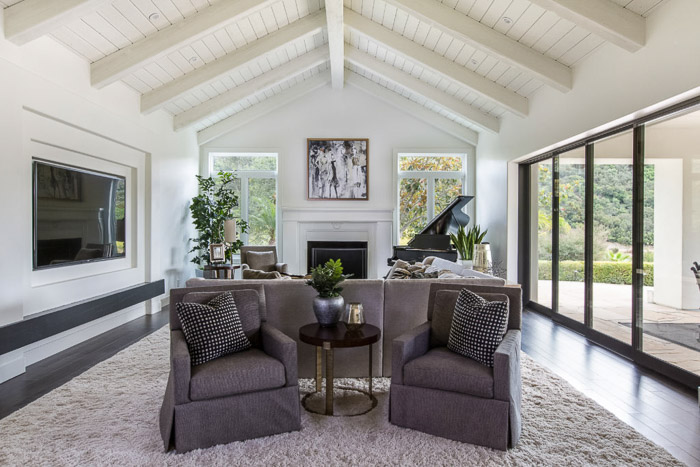 Gorgeous interior photography of the interior of a naturally lit living room, large windows, grey furniture and white walls.