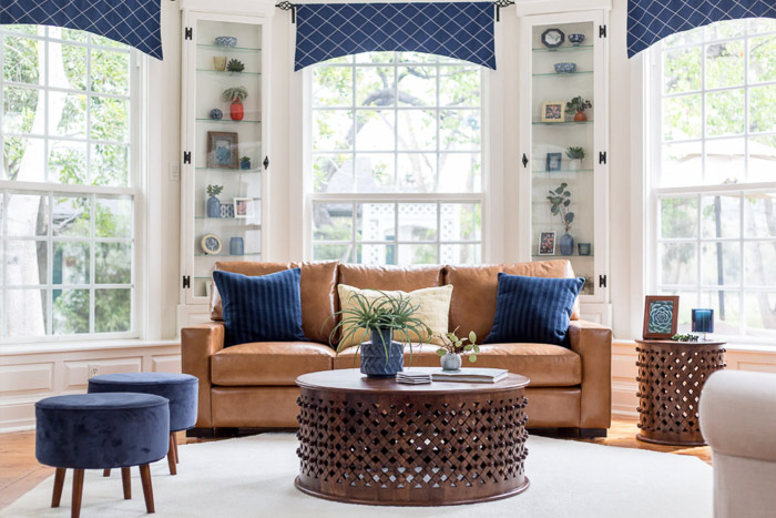 Gorgeous interior photography of the interior of a naturally lit living room, large windows, brown and blue furniture and white walls.