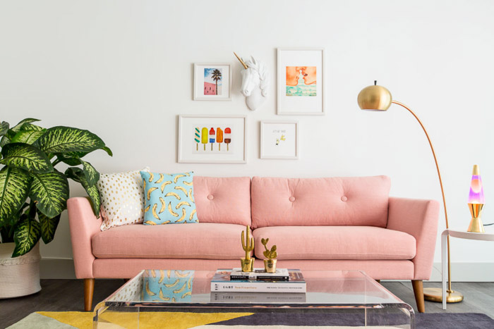 Gorgeous interior photography of the interior of a naturally lit room with pink sofa, picture frames and white walls.