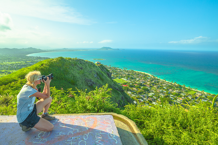 A female photographer taking pictures of a stunning landscape below