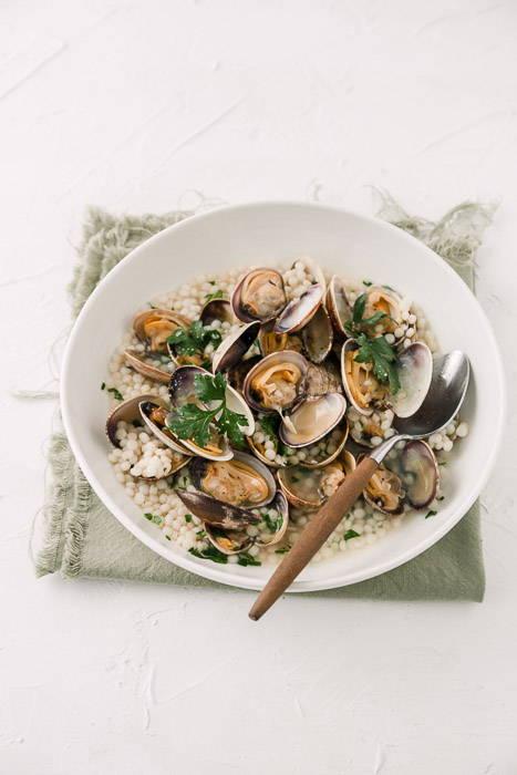 Overhead food photography of clams in a white bowl on white background. How to Use Lightroom for Editing Food Photography