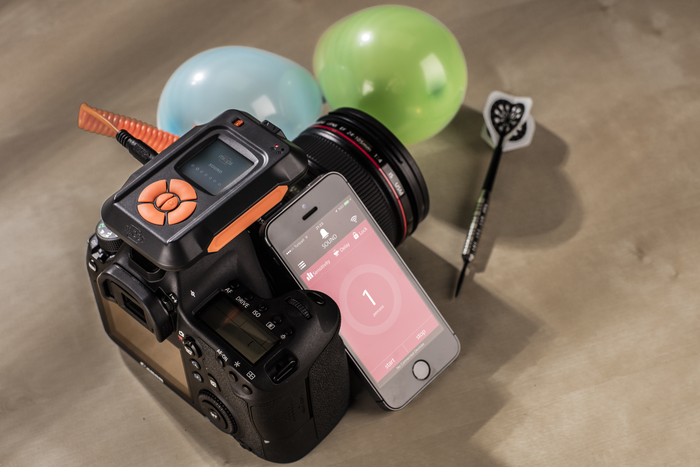 Still life photography of a DSLR camera fitted with MIOPS Smart Trigger beside balloons and a dart