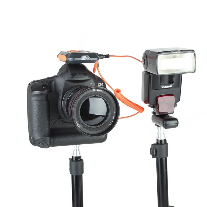 Image of a DSLR camera fitted with a MIOPS Smart Trigger beside external flash on white background