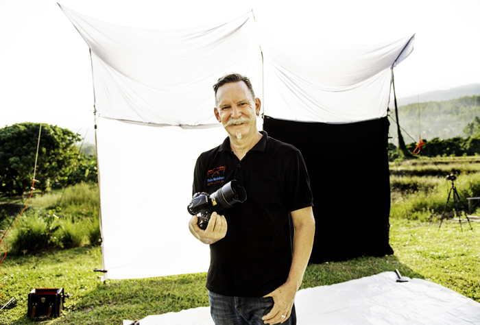 A photographer poses with his camera in front of his outdoor photography studio.