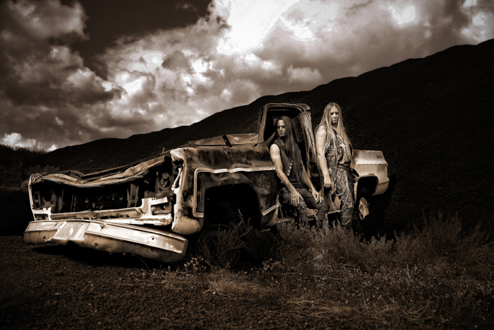 Monochrome photography of a couple leaning on a destroyed car.