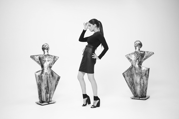 Black and white photography of a girl between two sculptures.