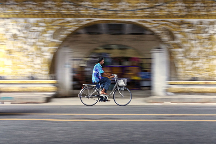 Street photography of a man riding a bicycle with blurry background.