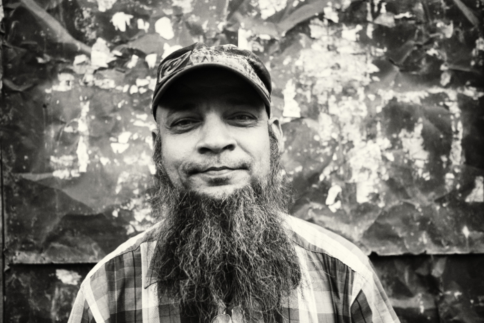 Black and white portrait of a man with cap and beard.