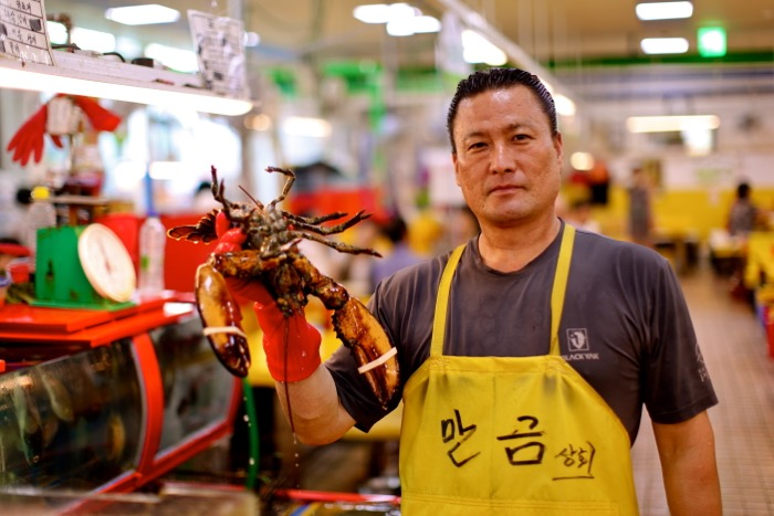 Portrait of a man in a fish market holding a lobster.
