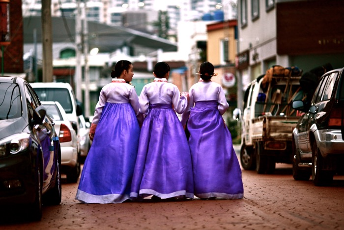 Street photography of three women in purple dresses walking down the street.