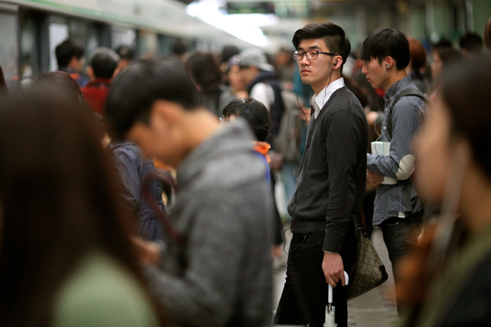 Street Photography of a crowd of people waiting for a train.