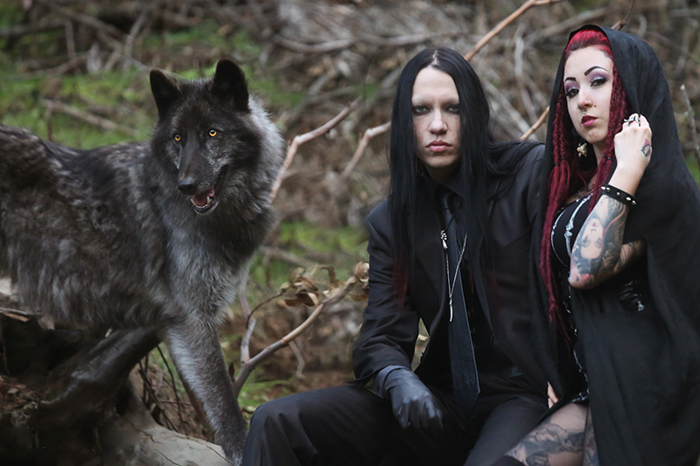 Portrait of a gothic couple beside a large dog.